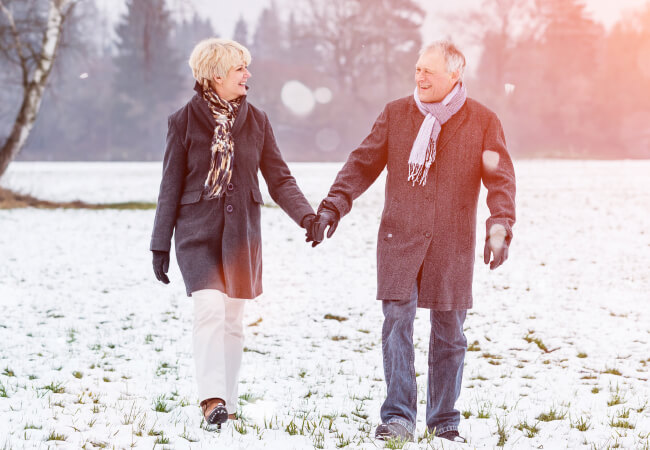 elderly couple walking in the snow